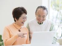 ノートパソコンに向かうシニア夫婦