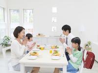 食卓で手を合わせる家族