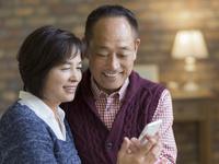 スマートフォンを見るシニア夫婦