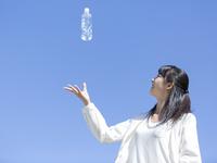 水の入ったペットボトルを投げる女性