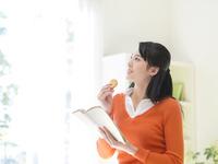 クッキーを食べながら本を読む女性