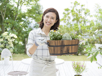 鉢植えを持つ40代の女性