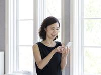 スマートフォンを操作する40代の女性