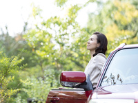 車の横に立つ日本人の女性