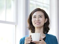 コーヒーカップを持つ40代の女性