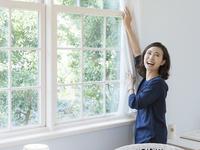 窓辺に立つ40代の女性