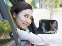 車の窓から顔を出す40代の女性