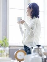 窓辺でコーヒーカップを持つ女性