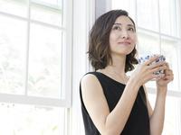窓辺でティーカップを持つ女性
