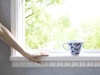窓辺に置かれたティ−カップと女性の手