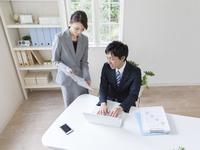 書類を見るビジネスマンとビジネスウーマン