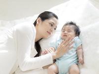 赤ちゃんと添い寝をする母親