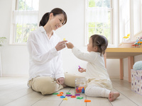 アルファベットブロックで遊ぶ女の子と母親