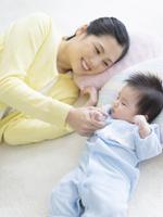 手を繋いで寝る赤ちゃんと母親