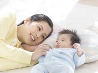 手を繋いで寝る母親と赤ちゃん
