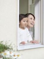 窓の外を見る母と子