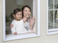 窓から手を振る母と子