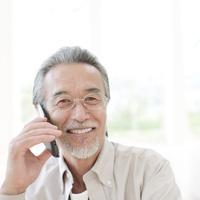 携帯電話を耳にあてるシニア男性