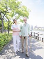 散歩をするシニア男性と介護士