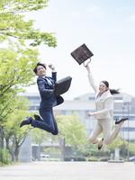 ジャンプをするスーツ姿の男女