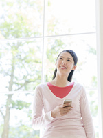 窓辺でスマートフォンを持つ女性