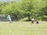 公園でサッカーをする親子