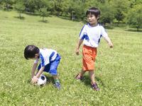 サッカーボールで遊ぶ兄弟