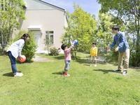 庭でボール遊びをする日本人家族