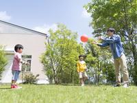庭でボール遊びをする父と兄弟