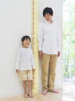 身長計の横に立つ日本人親子