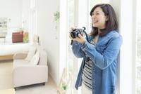デジタルカメラを持って笑う女性