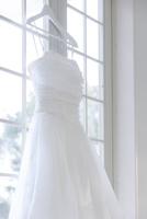 窓辺にかけられたウエディングドレス