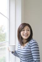 窓辺でカップを持つ女性