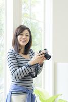 カメラを持って微笑む女性