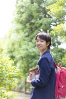 教科書を持って振り返る若者男性 11004120339| 写真素材・ストックフォト・画像・イラスト素材|アマナイメージズ