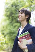 教科書を持って笑う若者男性 11004120341| 写真素材・ストックフォト・画像・イラスト素材|アマナイメージズ