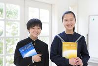 教科書を抱える中学生男女