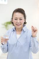 水の入ったグラスとサプリメントを持つ女性