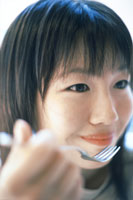 フォークで食べる女の子