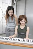 シンセサイザーを弾く女性 11006000621| 写真素材・ストックフォト・画像・イラスト素材|アマナイメージズ