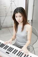 シンセサイザーを弾く女性 11006000626| 写真素材・ストックフォト・画像・イラスト素材|アマナイメージズ