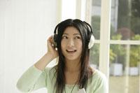 ヘッドフォンをあてて音楽を聴く女性