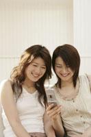 携帯電話を見る女性 11006001068| 写真素材・ストックフォト・画像・イラスト素材|アマナイメージズ