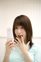 携帯電話を見る女性 11006001080| 写真素材・ストックフォト・画像・イラスト素材|アマナイメージズ