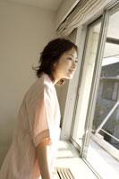 窓辺に立つパジャマ姿の女性