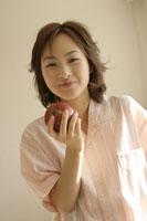 りんごを持つパジャマを着た女性