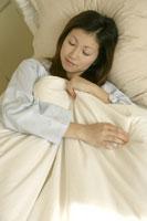 布団に包まってベッドで寝る女性 11006001148| 写真素材・ストックフォト・画像・イラスト素材|アマナイメージズ