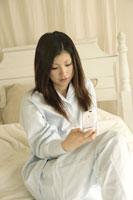 ベッドで携帯電話を見る女性 11006001153| 写真素材・ストックフォト・画像・イラスト素材|アマナイメージズ