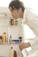 冷蔵庫を見る男性