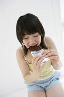 チョコレートを食べる10代の女の子